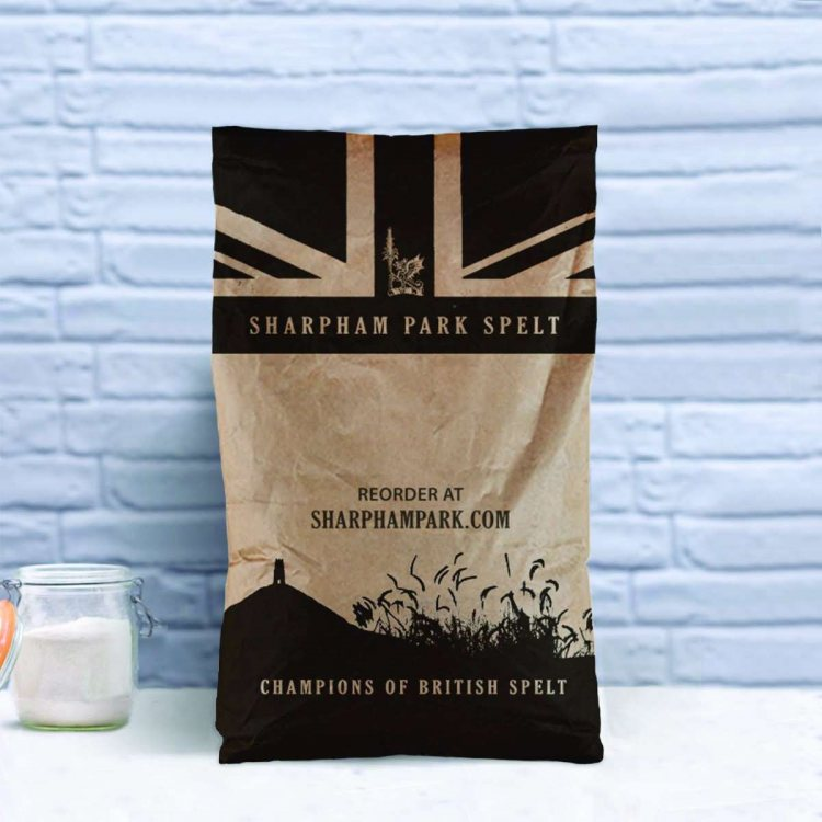 Photo showing the Sharpham Park Organic Emmer Flour large bag on a white surface with an open glass