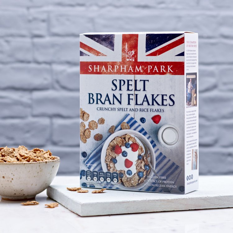 Photo showing the Sharpham Park Spelt Bran Flakes cereals in a box on a white surface with a bowl of